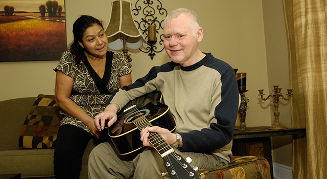 Man with guitar and his support worker