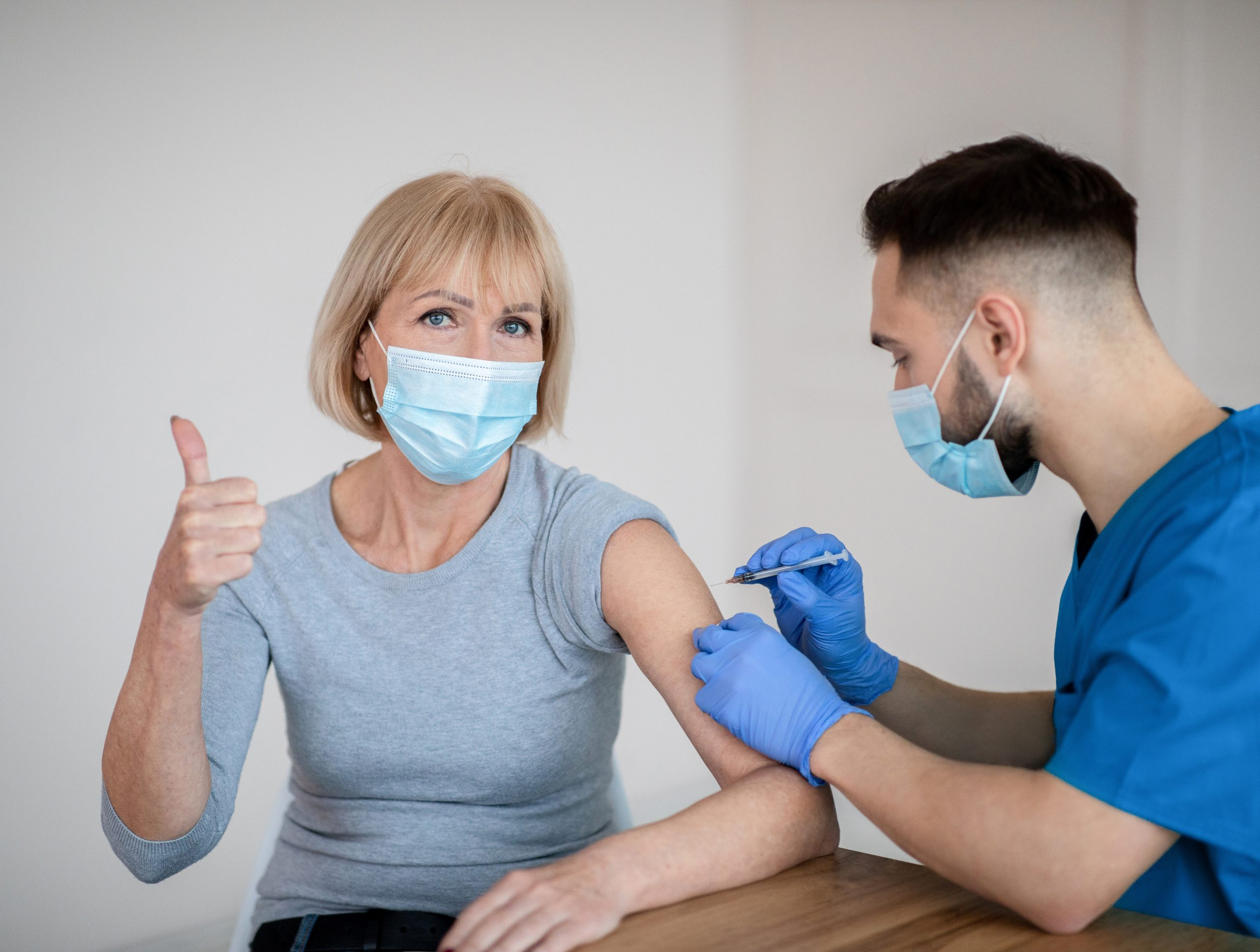 Mature woman in face mask approving of covid-19 vaccination, showing thumb up during coronavirus vaccine injection